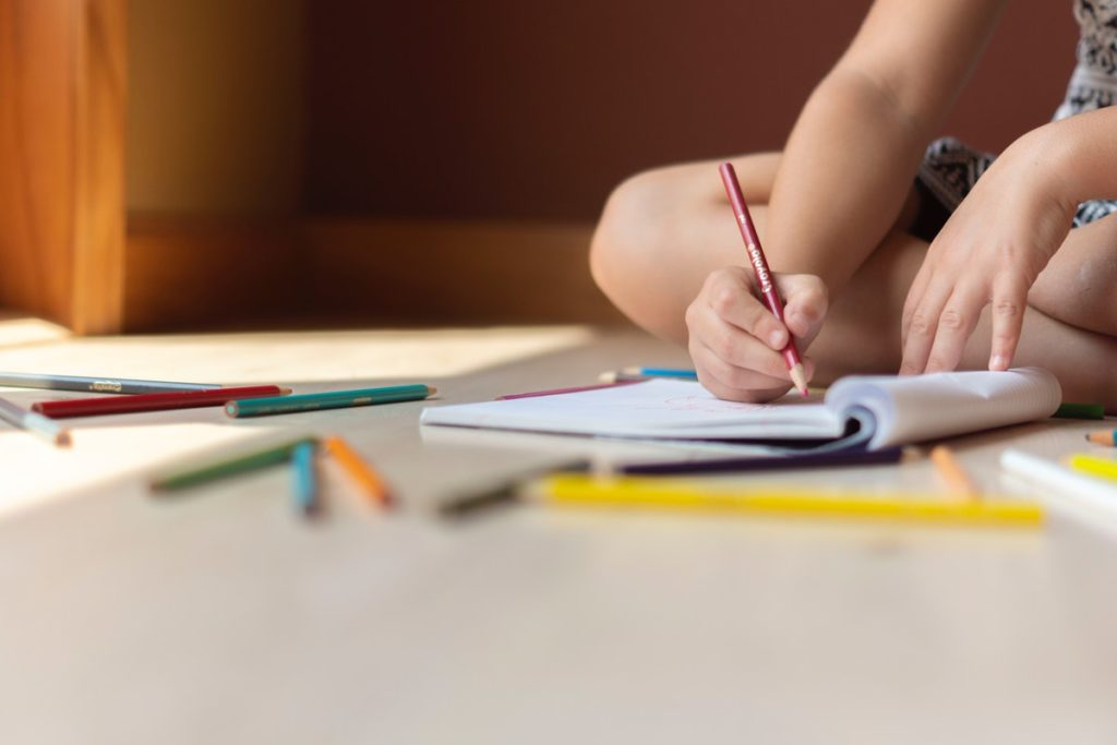 child writing on a notebook