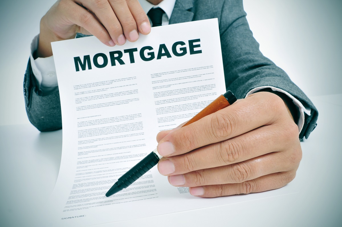 Mortgage form being held with a pen