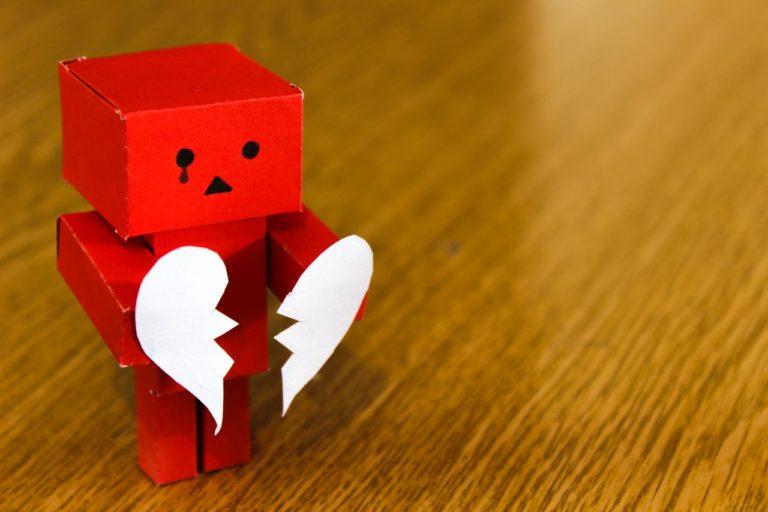 robot toy holding broken heart paper cutout