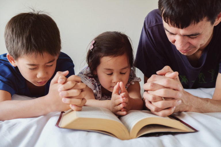 father and children praying