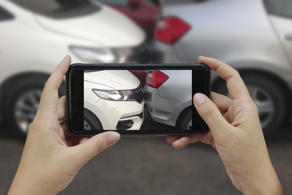 woman taking picture of car crash